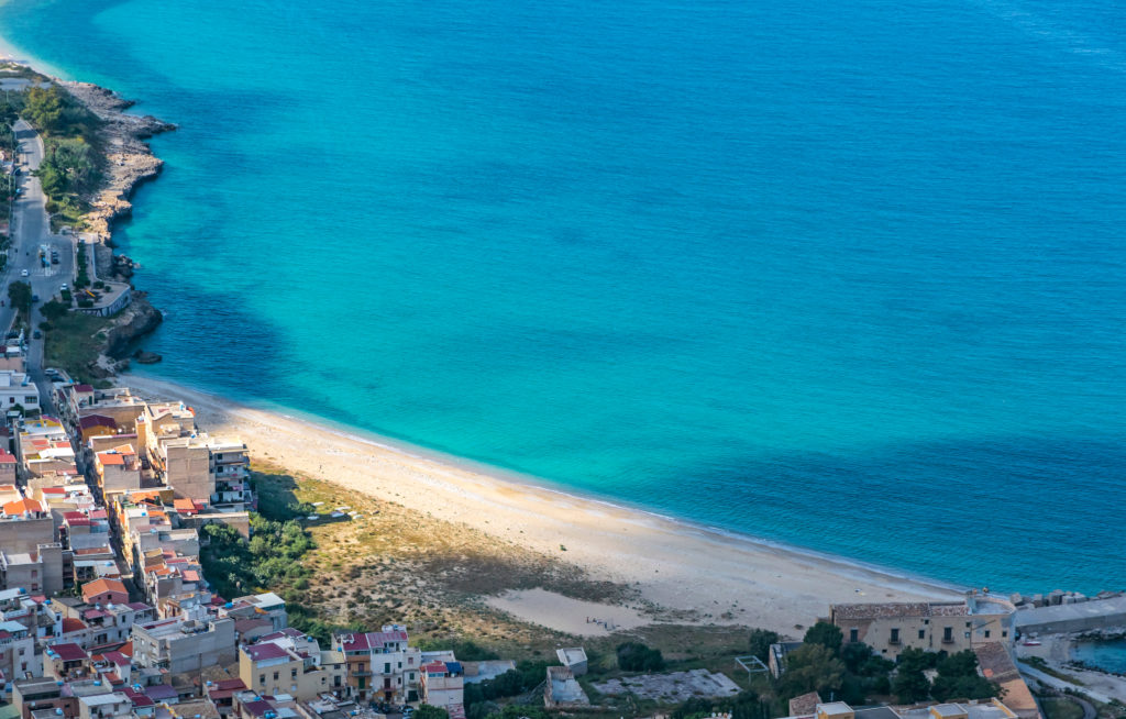 Aerial view of the Vergine Maria Beach in Palermo city, Sicily, Italy. Is a small triangle of golden sand set between the houses, dominated by the massive and evocative mass of Mount Pellegrino
