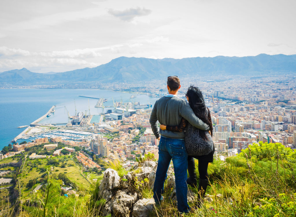 Couple holding each other, enjoying view above city of Palermo on top of Mount Pellegrino, Palermo, Sicily, Italy.