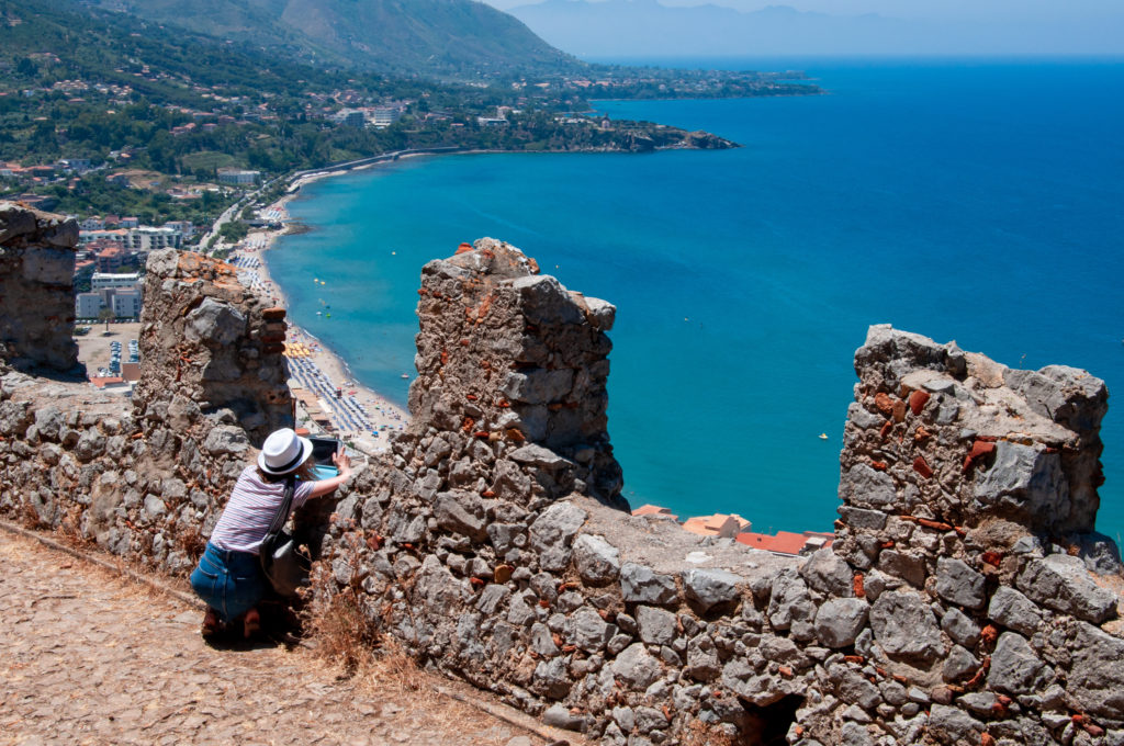 A young girl photographs a beautiful landscape of the Mediterranean Sea from the cliff of La Rocca in the city of Cefalu on a sunny summer day. Sicily. Italy.