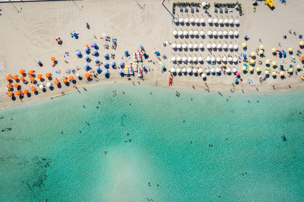 Aerial view of San Vito Lo Capo,Sicily white sand beach. Sun loungers, umbrellas and the sea, view from a quadrocopter