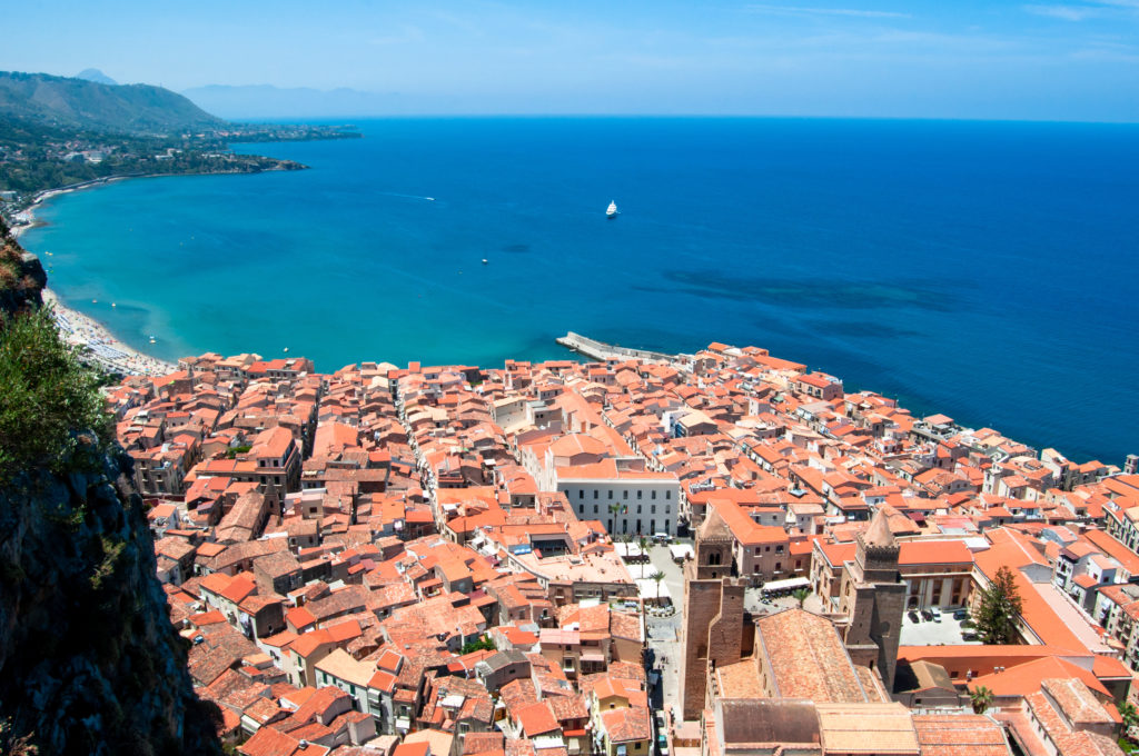 Beautiful view of the Sicilian city of Cefalu, Cathedral and the Mediterranean Sea from Mount La Rocca on a sunny day with blue sky. Sicily. Italy. Horizontal view.