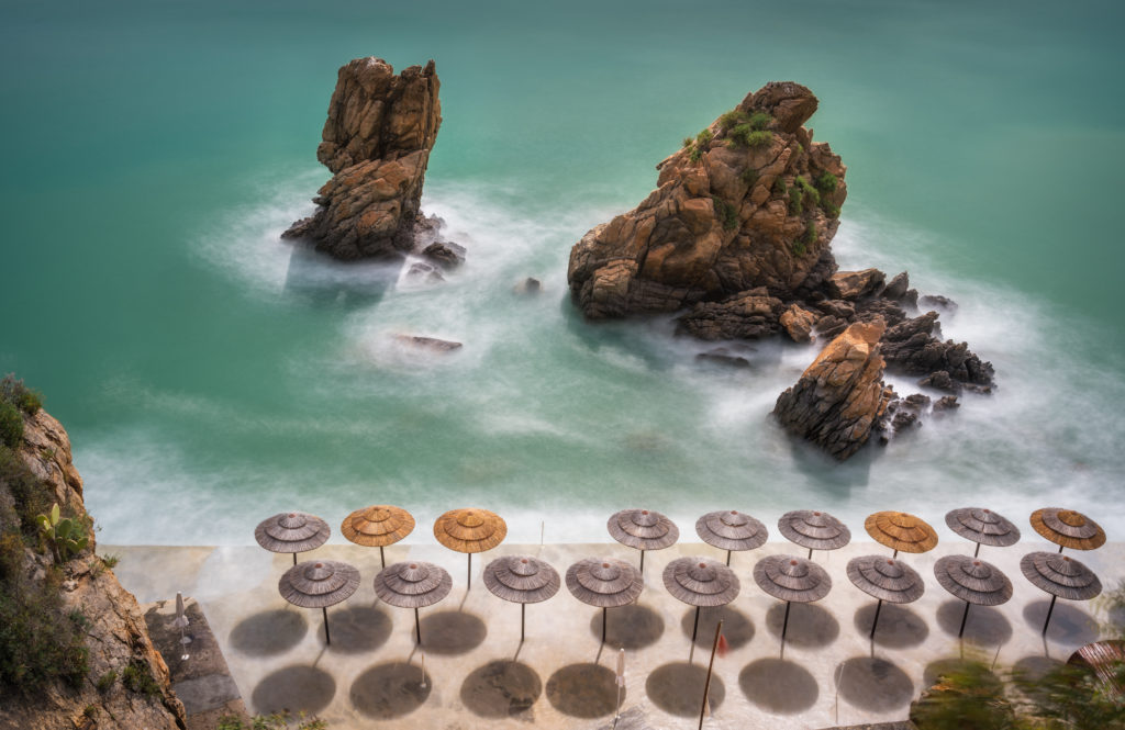 Cozy beach umbrellas, Tyrrhenian sea and the rocks. Long exposure shot of La Kalura bay, Cefalu, Sicily, Italy