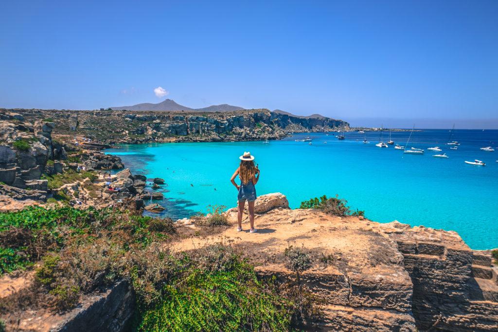 Girl in Cala rossa Bay. Beach in Favignana Island.