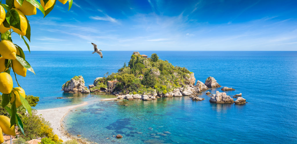 Isola Bella is small island near Taormina, Sicily, Italy. Narrow path connects island to mainland Taormina beach in azure waters of Ionian Sea. Bunches of fresh yellow ripe lemons on foreground.