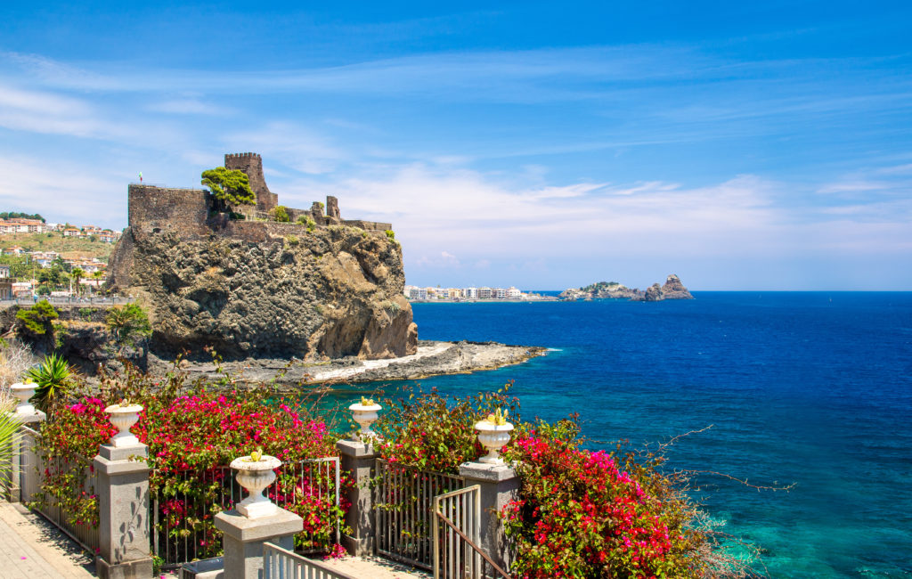 Norman old medieval Castle Aci Castello with stone walls on rock coast near water of mediterranean sea and fence with red flowers foreground, Catania, Sicily, Southern Italy