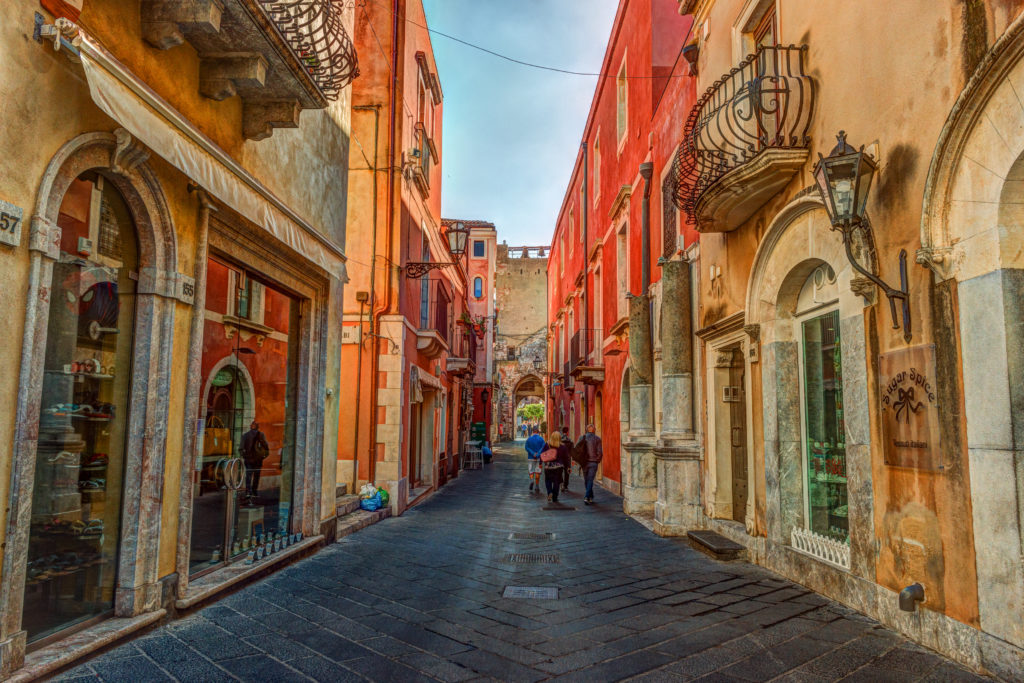 Stara ulica w Taormina, Sycylia, Włochy. Architektura z łukami i starym chodnikiem.
