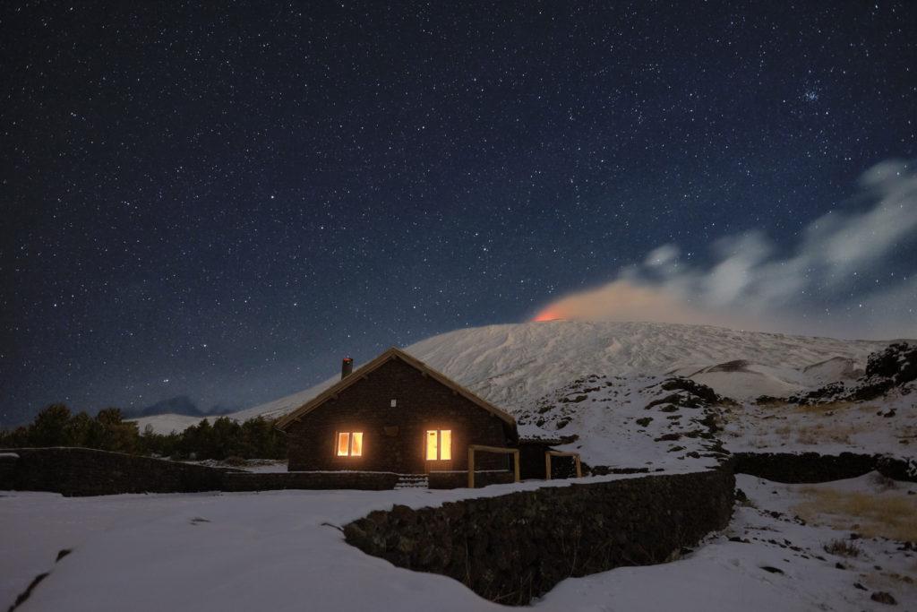 starry night on Galvarina Refuge with windows glowing under snowy Etna Volcano, Sicily