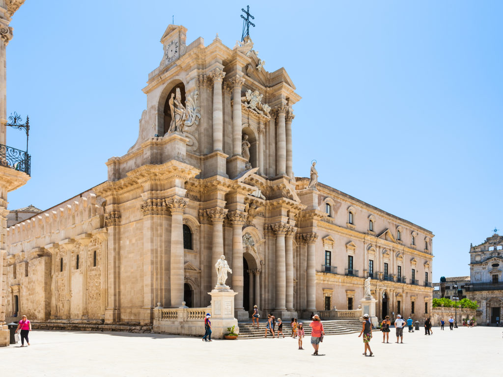 SYRACUSE, ITALY - JULY 3, 2011: people near Cathedral on piazza Duomo in Syracuse city in Sicily. The city is a historic town in Sicily, the capital of the province of Syracuse.