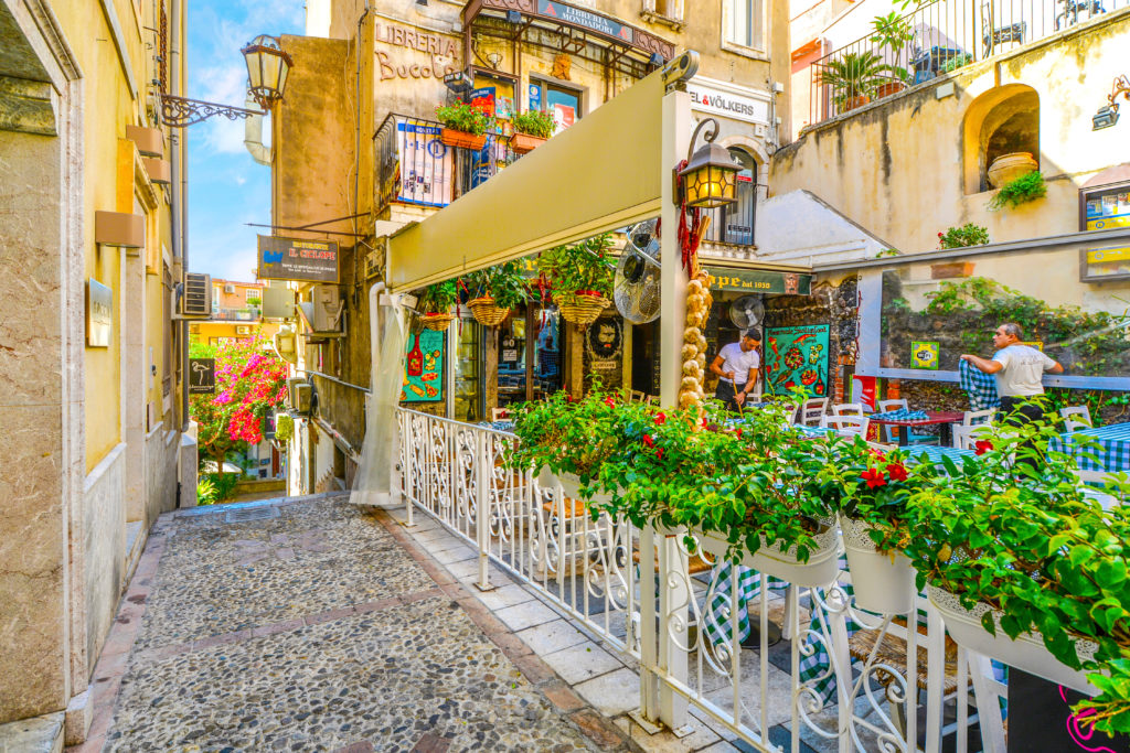 Taormina, Italy - September 15 2018: Restaurant workers prepare for the day at a colorful and picturesque cafe just off of Corso Umberto, the main street in Taormina Italy on the island of Sicily.