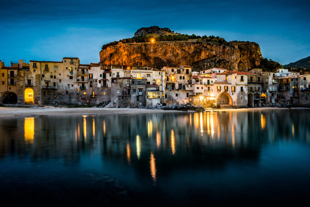 Widok na nawyk i stare domy w Cefalu w nocy, Sycylia. Piękny krajobraz starego włoskiego miasta. Fotografia podróżnicza.