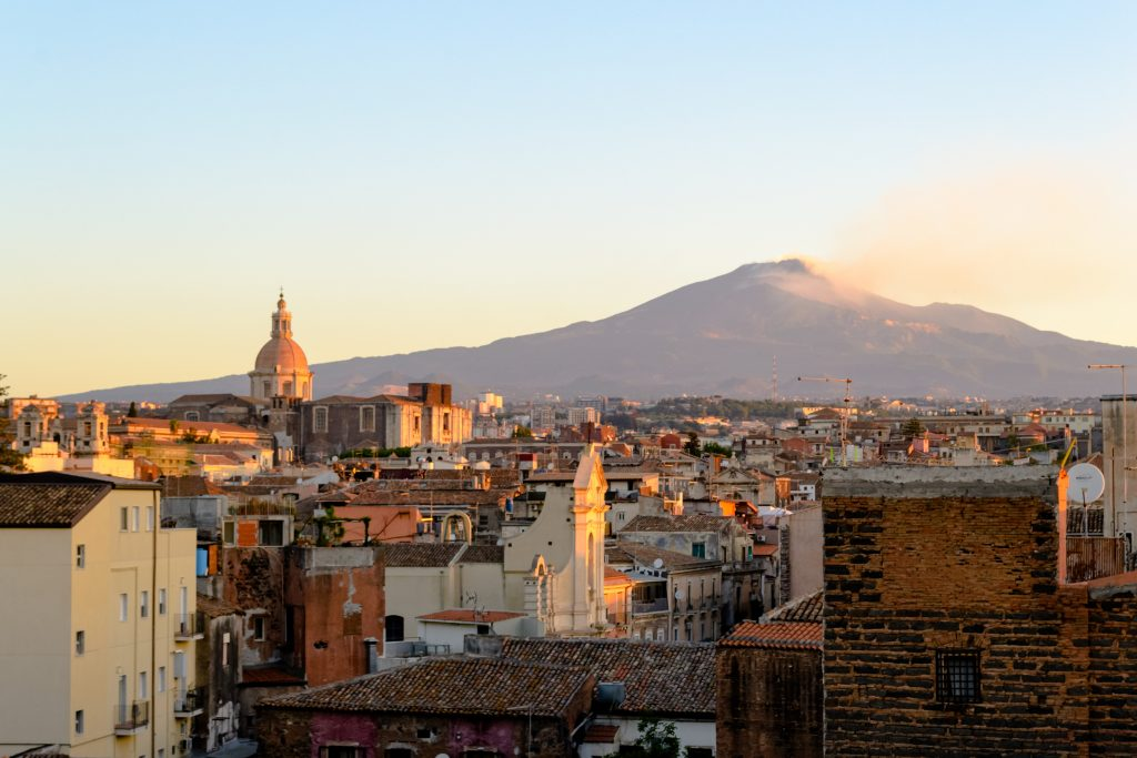 Catania, Sicily in Italy. Aerial view of the city roofs at dawn with the incredible Etna vulcano smoking in the background, nice warm colors and soft light