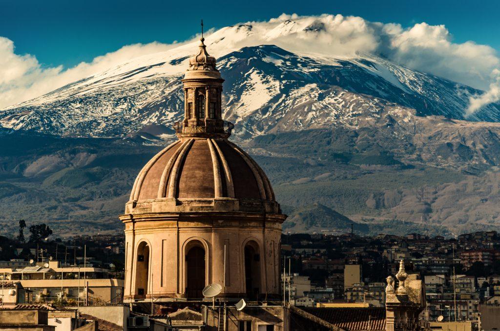 Kopuła katedry w Katanii na tle wulkanu Etna w śniegu.. Widok miasta Katania z widokiem na wulkan Etna, Sycylia, Włochy. Katania wpisane na Listę Światowego Dziedzictwa UNESCO.