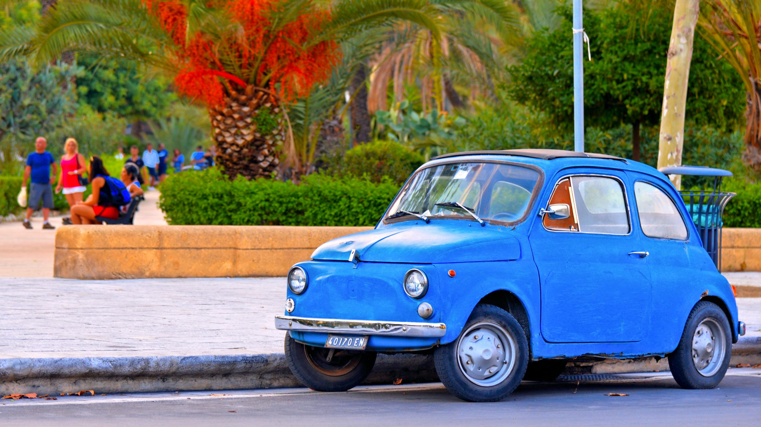 24.08.2018. Palermo, Sicily Italy - vintage blue car Fiat 500 on the  street in front of city park and people relaxing in Palermo in South Italy