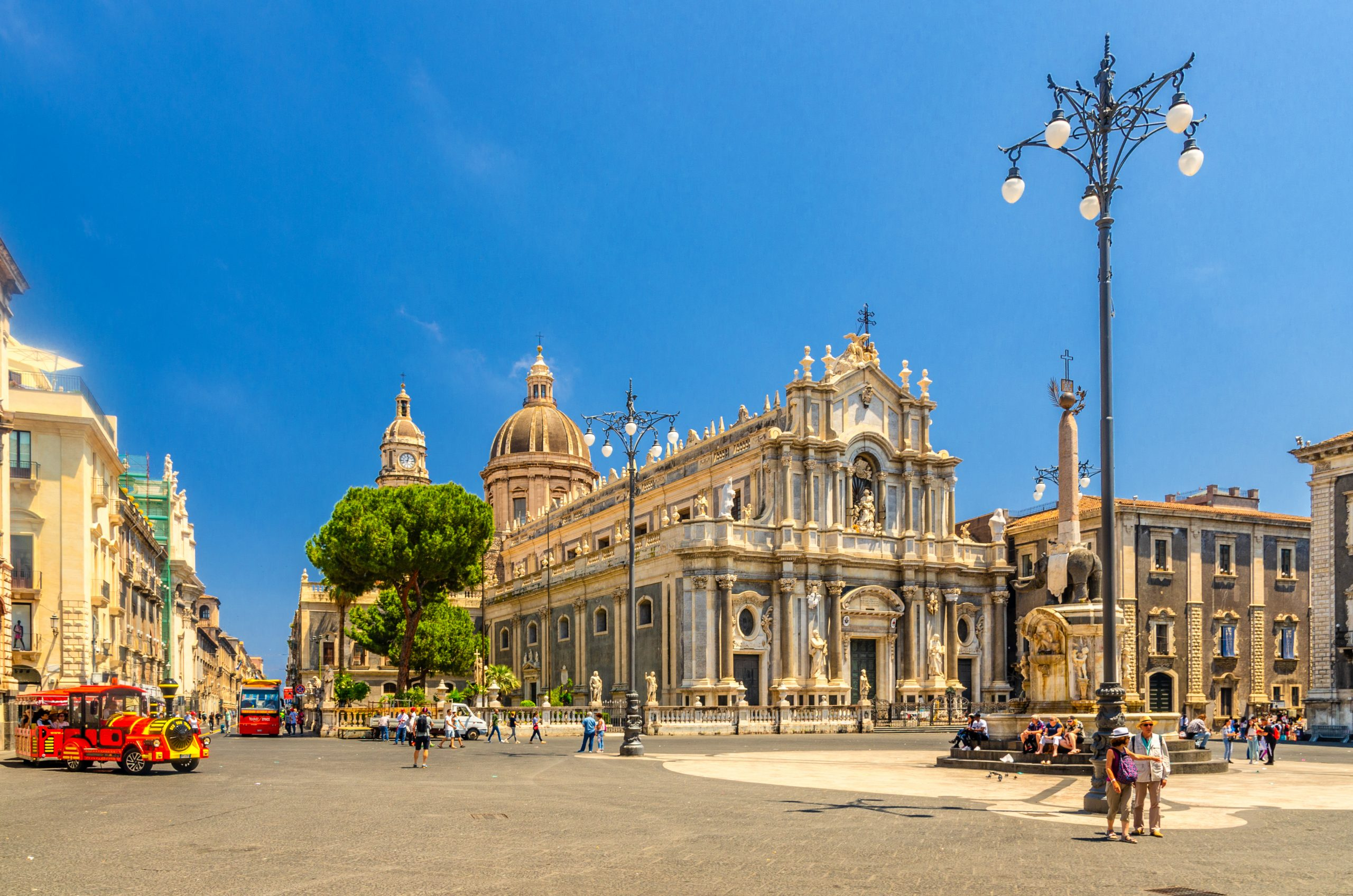 Italy, Catania, May 13, 2018: Elephant Statue fountain, Cathedral of Santa Agatha, touristic red train and walking people on Piazza del Duomo square in Catania historical city centre of Sicily island