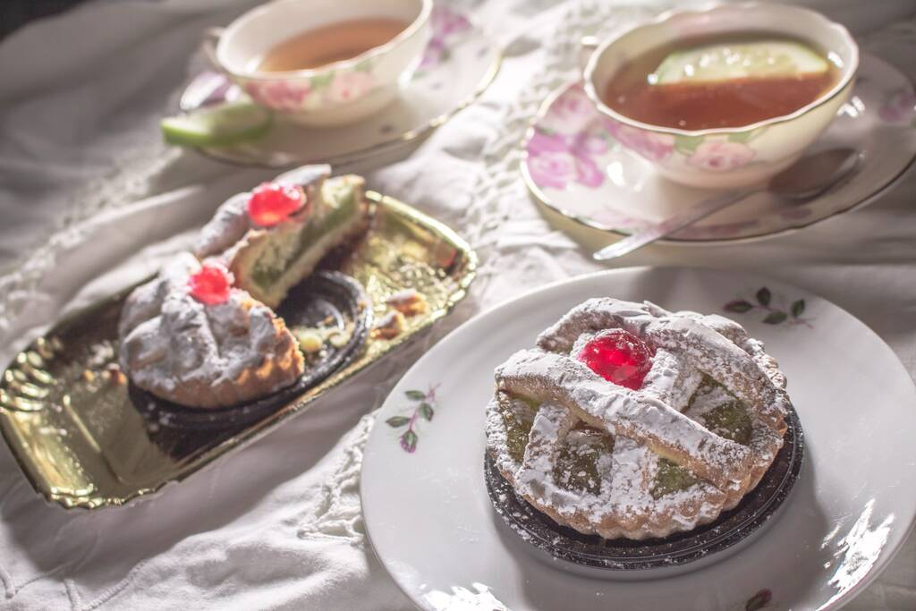 """A dessert from Palermo called """"Maria Stuarda"""". A small tart with Sicilian pumpkin jam and candied cherry on a plate, another tart cut in two on a tray and two cups of tea on the background"""