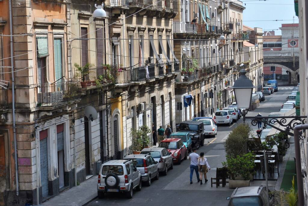 Everyday streetscape with young couple walking past old apartment buildings on a narrow, one-way street in Catania, Sicily, Italy.