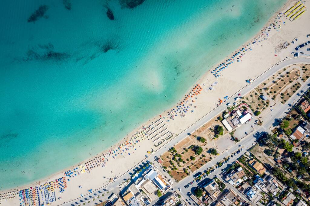 Aerial view of San Vito Lo Capo,Sicily white sand beach. Sun loungers, umbrellas, city houses and the sea, view from a quadrocopter