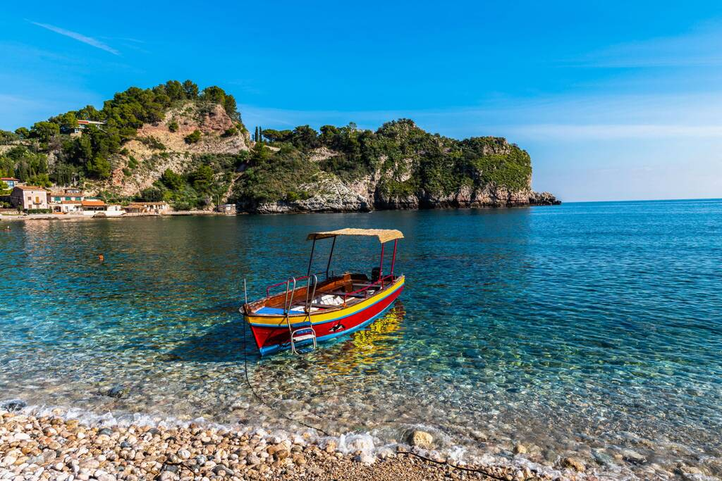 Boat on the sea at the beach with clean water, Isola Bella near Taormina in Sicily, Italy