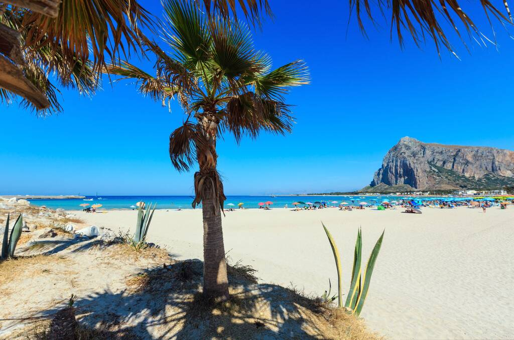 Paradise Tyrrhenian sea bay, San Vito lo Capo beach with clear azure water and extremally white sand, and Monte Monaco in far, Sicily, Italy. People unrecognizable.