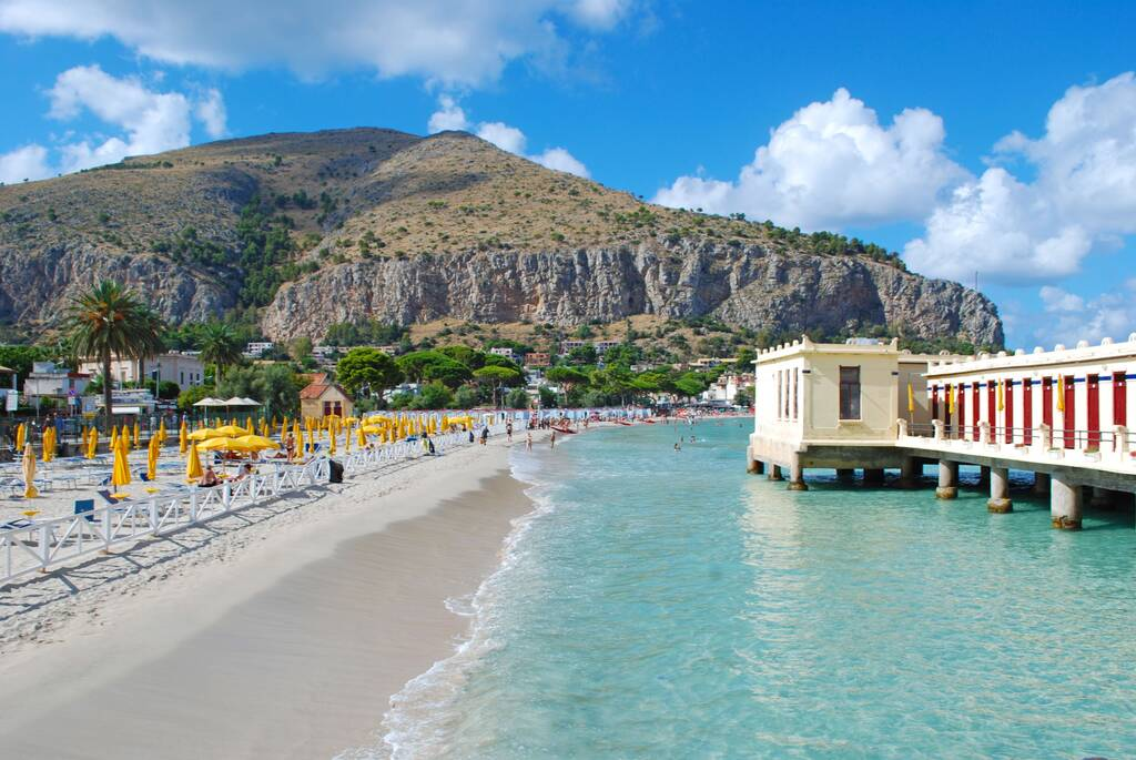 Sunny beach in Mondello, Italy near Palermo with crystal clear sea water and a beautiful view to a nearby hillside.