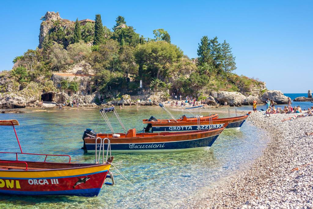 Taormina, Italy - May 29, 2015: Tourists and excursion boats at Isola Bella in Sicily