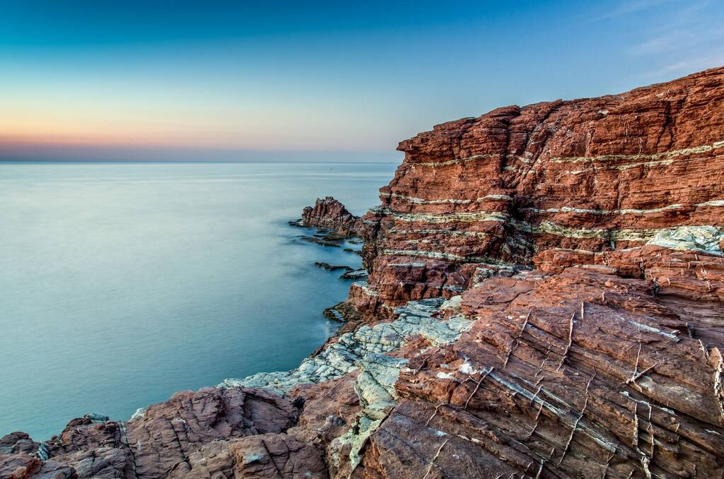Typical red rock formations of Cala Rossa in Terrasini, Province of Palermo, Sicily, Italy